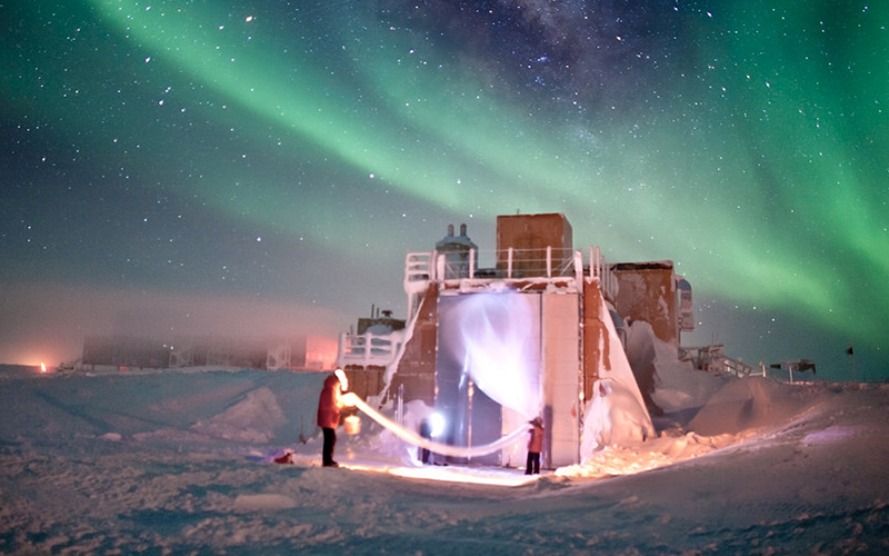 A plastic balloon being launched at the South Pole, with Auroras in the background. Credit: Patrick Cullis, CIRES/NOAA